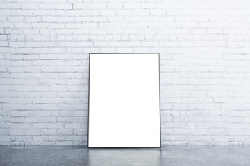Blank white picture frame on concrete floor in empty room with w