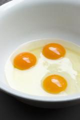 Drei aufgeschlagene rohe Eier in einer weißen Schüssel