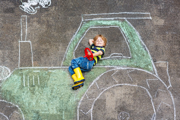 Little boy having fun with tractor picture drawing with chalk