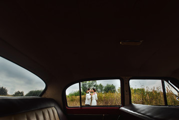 unusual view of stylish bride and happy groom through red retro