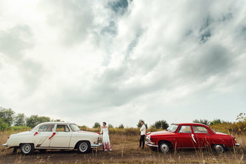 stylish bride and happy groom near  two retro cars on the backgr