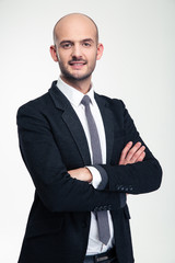 Cheerful attractive young business man standing with crossed arms