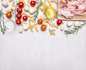 Ingredients for cooking fusilli pasta with bacon vegetables, spices and herbs  border, place for text on wooden rustic background top view