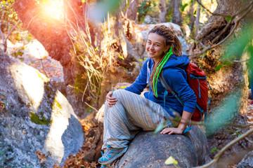 Cute Girl sitting on fallen Tree Stalk in wild Forest