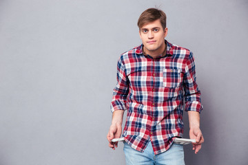 Poor handsome young man in checkered shirt showing empty pockets Wall mural
