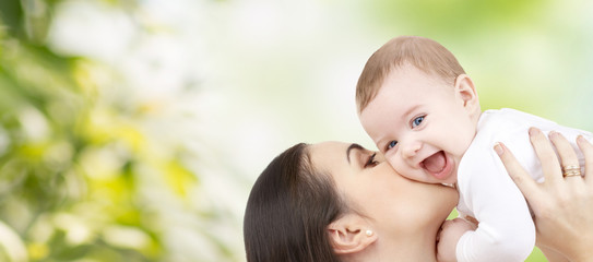 happy mother kissing baby over green background