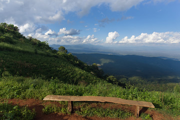 Lonely chair with grass, mountain and cloudy sky view of Chiangmai