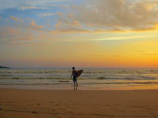 Surfer silhouette at ocean sunset beach