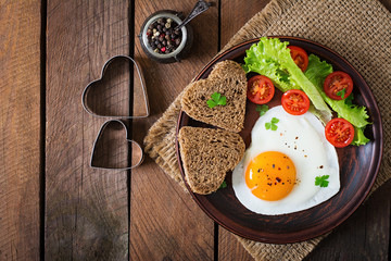 Fototapeta Breakfast on Valentine's Day - fried eggs and bread in the shape of a heart and fresh vegetables. Top view obraz