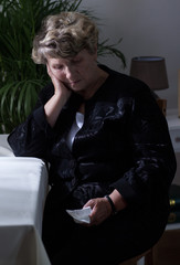 Lonely widow crying after funeral
