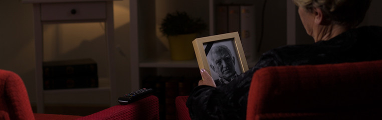 Senior widow holding photo