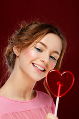Valentine's Day. Beautiful young girl with a red heart in his hands. laughs girl with heart in her hands. Young woman with red heart on red background. close up