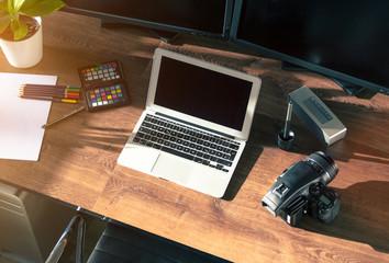 Desktop shot of a modern Digital Photo Camera with Laptop