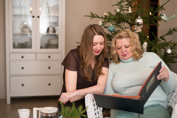 Two women looking photo album near a Christmas tree. Mother with daughter.