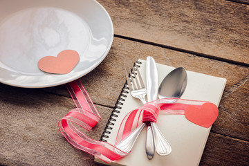 Valentines day table setting with plate, knife, fork, red ribbon