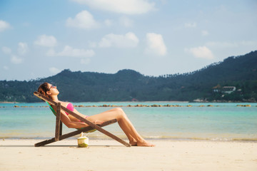 Beautiful, tranquil lady tanning while lying in the lounge with a fruit cocktail on the beach.
