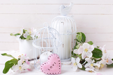 Spring apple blossom, candles in decorative bird cages and littl