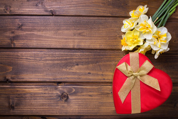 Red gift box with bow  and fresh  white and yellow narcissus flo