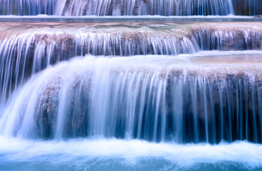 Clean blue water flows on cascades of waterfall
