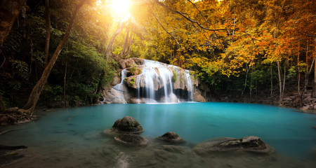 Waterfall in autumn forest with bright sun light and small natural lake with clear blue water