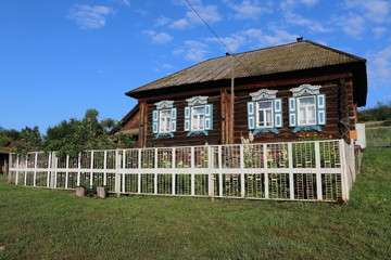 Wall Mural - Very old wooden house in the remote Russian village in the summer against a blue sky