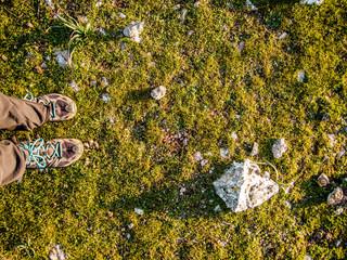 Wanderschuhe auf grüner Wiese mit Steinen