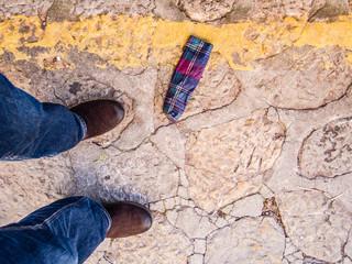 Aufsicht auf braune Stiefel auf Natursteinpflaster mit Regenschirmhülle