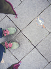 Selfie von grünen Stiefeln auf grauem Betonpflaster mit Fußgänger-Plakette