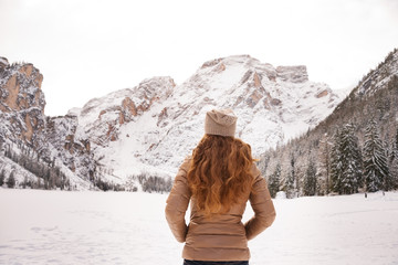 Seen from behind woman outdoors among snow-capped mountains