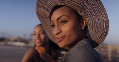 Black women best friends looking out over ocean while standing o