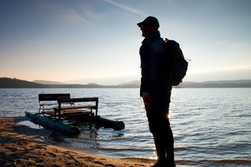Tall tourist with backpack walk on beach at pedal boat in the sunset. Autumn at sea