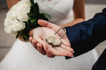 The lock in hands of newlyweds, .Place for text on lock. Bouquet on background bokeh