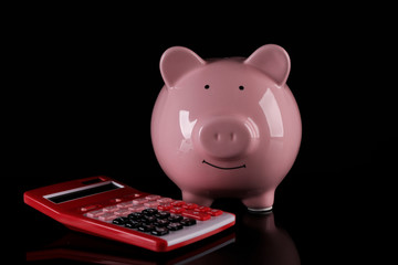 Piggy bank with calculator on dark background
