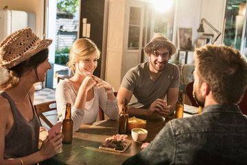 Friends having a drink and playing cards on a sunny evening. The