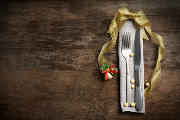 Christmas serving cutlery with a napkin on a wooden background