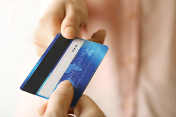 Hands holding blue credit card on white background