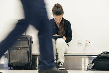 Young backpacker woman waiting for her flight.