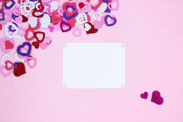 Blank white sign with collection of hearts on pink fabric background