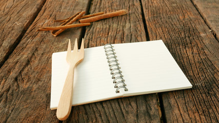 The blank earth tone note book and wooden fork with cinnamon on the old dark brown wooden planks.