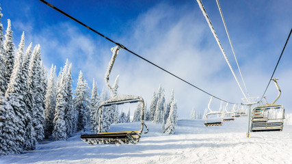 Wall Mural - Empty, snow and ice covered ski lift chairs on a cold winter day under partly blue skies at the village of Sun Peaks in the Shuswap Highlands of central British Columbia, Canada