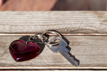 key with a heart trinket on wooden background