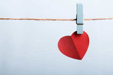 Red heart hanging on line
