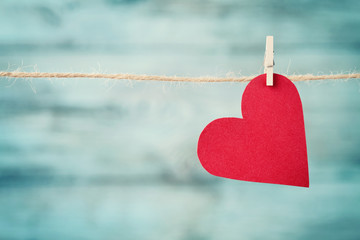 Paper heart hanging on string against turquoise wooden background for Valentines day, retro instagram filter effect