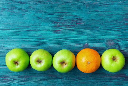 Green apples and one orange over rustic wooden background