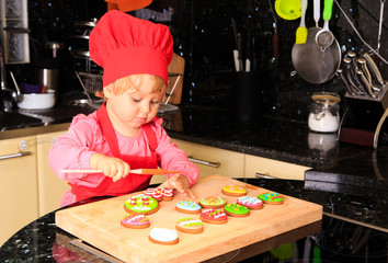 cute little girl making easter cookies in kitchen
