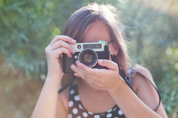 Beautiful young girl taking pictures with a old vintage camera