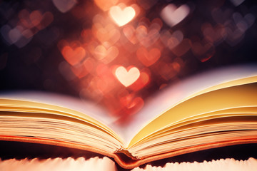 Open book against heart shaped bokeh, Valentines day concept