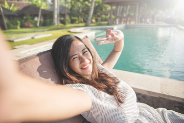woman relaxing next to the pool and taking selfie