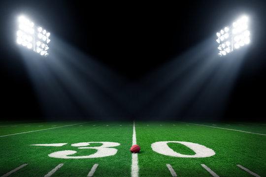 Football field at night with stadium lights