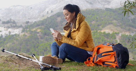 Smiling female hiker using her phone